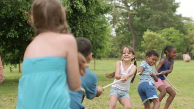 glückliche schulkinder spielen tauziehen im park - ferienlager stock-videos und b-roll-filmmaterial