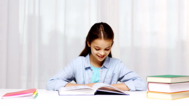 happy school girl with books writing to notebook at home video