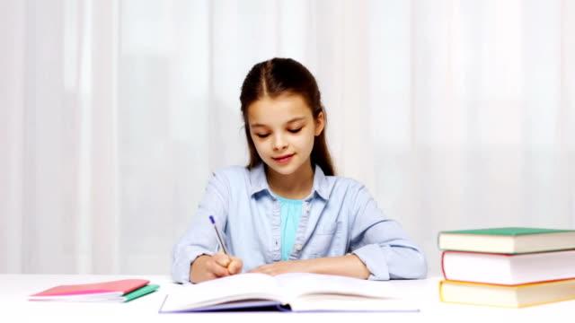 mutlu liseli kız evde not defterine yazma kitaplar - çalışma kitabı stok videoları ve detay görüntü çekimi