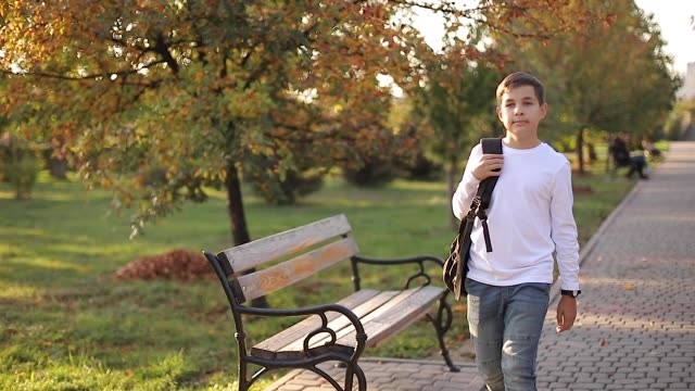 Happy schoolboy go back home after lessons. Teenager in white shirt denim jeans with backpack Happy schoolboy go back home after lessons. Teenager in white shirt denim jeans with backpack. sweatshirt stock videos & royalty-free footage