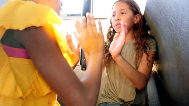 vídeos y material grabado en eventos de stock de feliz colegiala jugar aplaudiendo juego en el autobús escolar - escuela media
