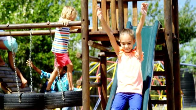 Colegiala feliz jugando en el tobogán en el patio - vídeo