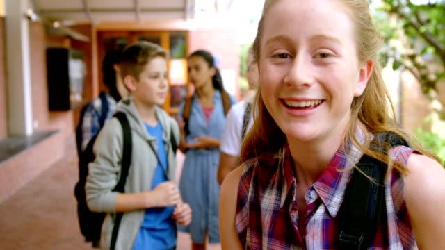 Happy schoolgirl standing in school premises 4k video