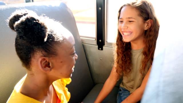 vídeos y material grabado en eventos de stock de happy colegialas disfrutan jugando aplaudiendo juego mientras que en el autobús escolar - autobuses escolares