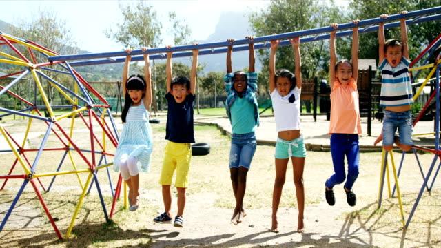 Happy schoolkids hanging on monkey bar video