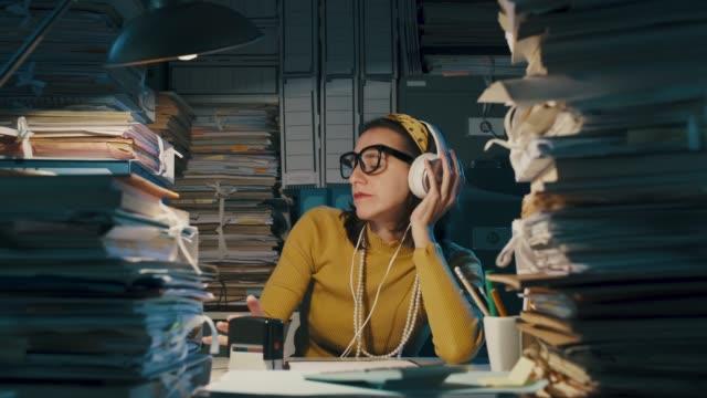 glückliche sekretärin hört musik im büro - rock stock-videos und b-roll-filmmaterial