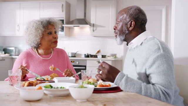 vídeos de stock e filmes b-roll de happy senior black couple talking and enjoying their sunday dinner together at home, close up - jantar assado