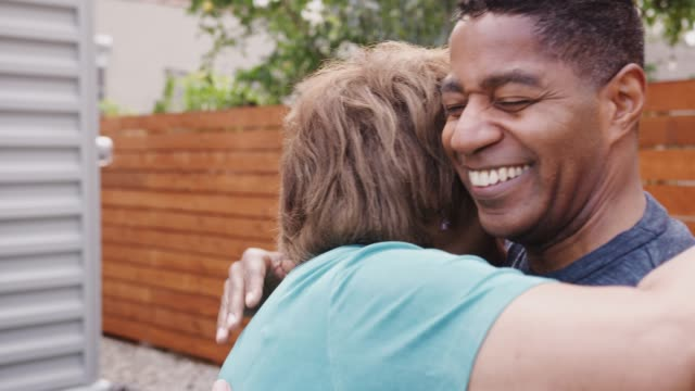 Happy senior black woman and her middle aged son embracing, head and shoulders, close up