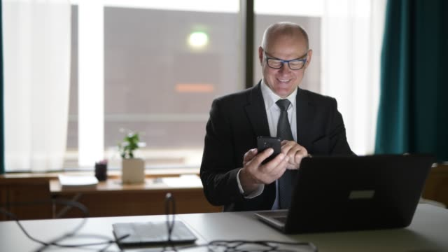 Homem de negócios sênior feliz que usa o telefone e o portátil no trabalho - vídeo