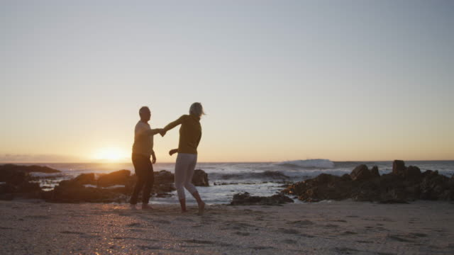 Happy senior couple at beach Front view of a senior Caucasian couple enjoying time in nature together, dancing on a beach at sunset, smiling, slow motion heterosexual couple stock videos & royalty-free footage