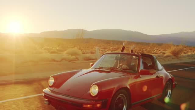 lyckliga senior paret firar med händer upp i luften under körning cabrioleter vid solnedgången - bekymmerslös bildbanksvideor och videomaterial från bakom kulisserna