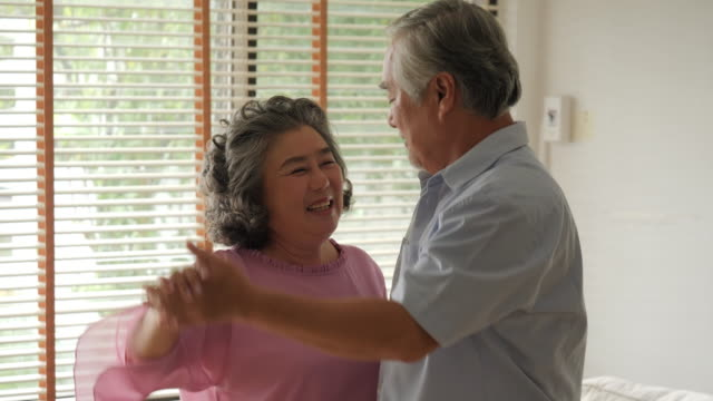 Happy senior couple dancing at home in slow motion.