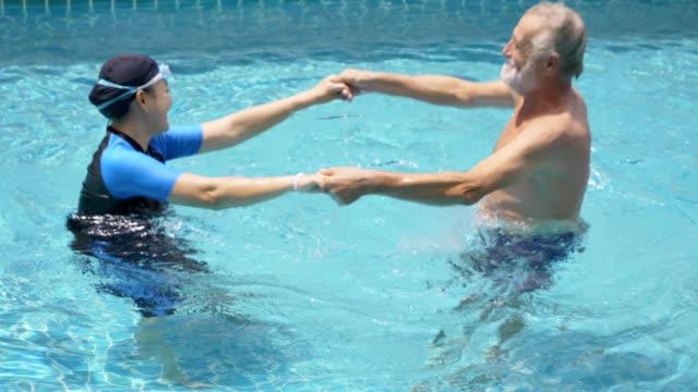 Happy senior couple dancing in pool
