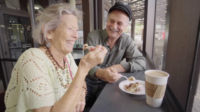 vídeos de stock e filmes b-roll de happy senior couple enjoy coffee and cake - bolo sobremesa
