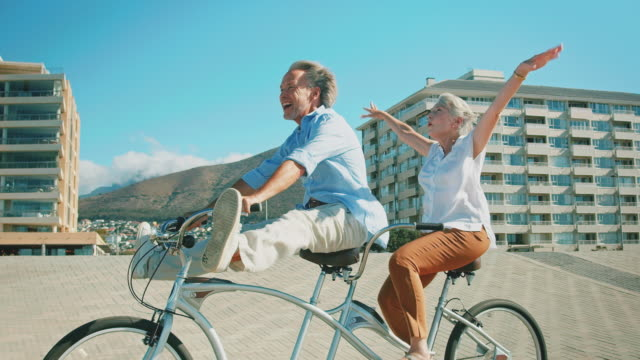happy senior couple enjoying on tandem bicycle - vacanze video stock e b–roll