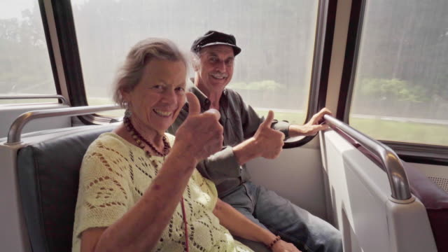 Happy Senior Couple Give Thumbs Up Signal on a Subway Train video
