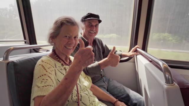 Feliz pareja Senior da pulgares para arriba de la señal en un tren de metro - vídeo