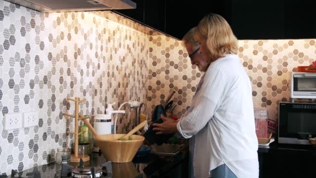 vidéos et rushes de couple aîné heureux ayant l'amusement dans la cuisine - vaisselle picto
