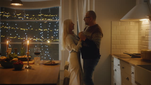 happy senior couple in love have romantic evening, dancing in kitchen, celebrating anniversary. elderly lovely husband, wife have romantic evening with wine, festive table in stylish kitchen interior - happy holidays filmów i materiałów b-roll