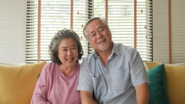 幸せな先輩カップルが居間でビデオ通話。技術と通信、シニアのライフ スタイルのコンセプトを持つ人々。 - 老夫婦点の映像素材/bロール