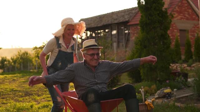 glückliches seniorenpaar spielt mit einer schubkarre an einem sonnigen tag - pensionierung stock-videos und b-roll-filmmaterial