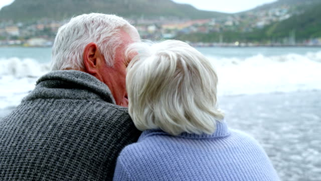 Happy senior couple pointing at view video