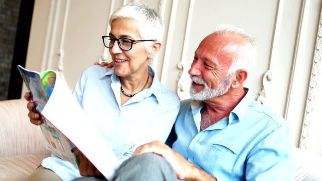stockvideo's en b-roll-footage met gelukkige senior paar lezen van een tijdschrift. - woman home magazine