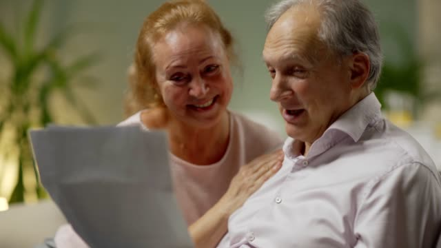 Happy senior couple reading financial documents at home and celebrating receiving inheritance certificate or lottery win