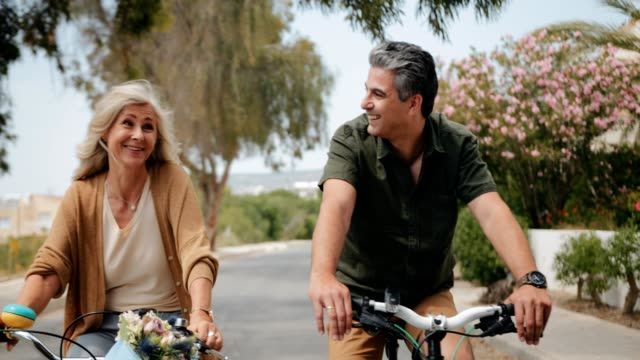 happy senior couple riding bikes in suburban street in spring - capelli grigi video stock e b–roll