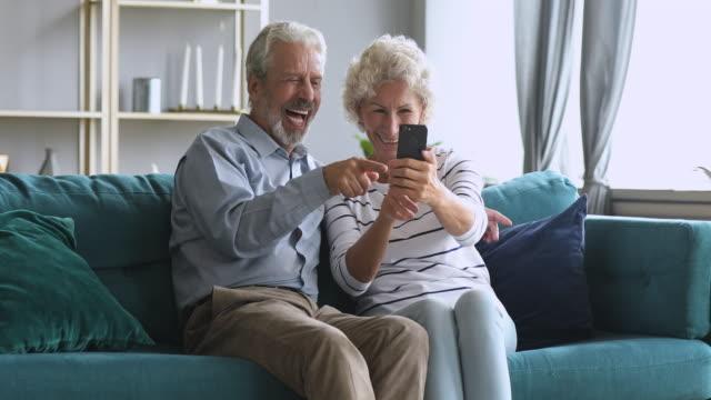happy senior couple take selfie on smart phone at home - babka dziadek i babcia filmów i materiałów b-roll