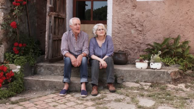 happy senior couple talking while sitting on porch - portico video stock e b–roll