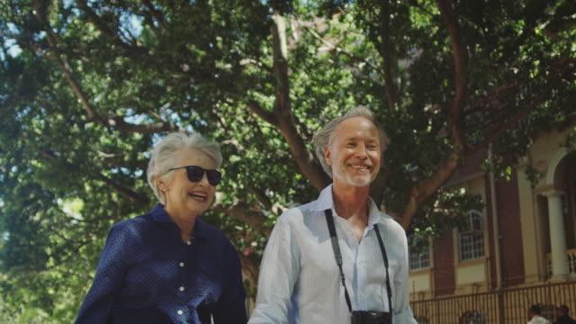 happy senior couple talking while walking in city - turysta filmów i materiałów b-roll