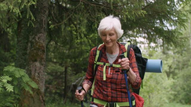 vídeos de stock e filmes b-roll de happy senior female hiker walking with trekking poles - old lady
