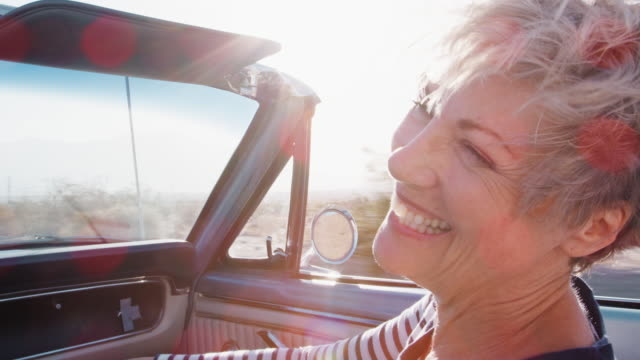 Happy senior female passenger in a convertible car, close up