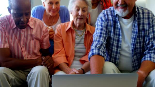 Happy senior friends having fun while using laptop 4k video
