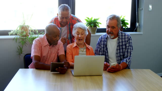 Happy senior friends interacting with each other while using laptop 4k video