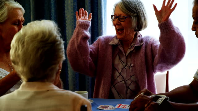 Happy senior friends playing cards 4k Happy senior friends playing cards in retirement home 4k playing card stock videos & royalty-free footage