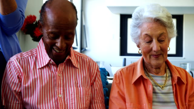 Happy senior friends using digital tablet on sofa video