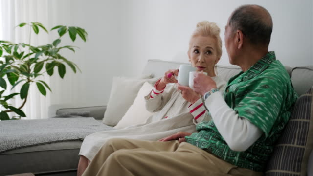 Happy Senior Japanese Couple Enjoying Coffee on the Sofa Senior Japanese husband and wife relaxing with morning coffee and discussing plans for the weekend. face to face stock videos & royalty-free footage