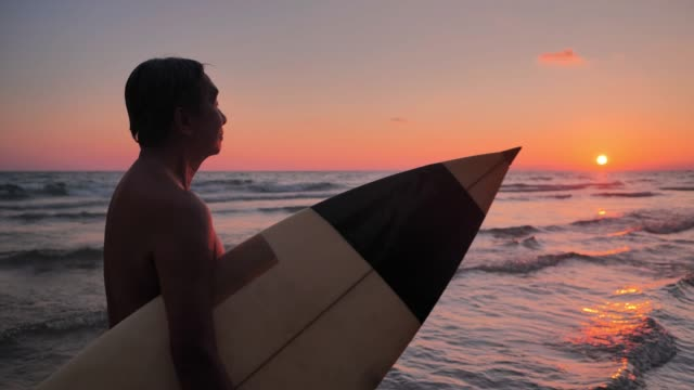 happy senior male surfer walking with surfboard on the beach during sunset.real bodies - body positive video stock e b–roll
