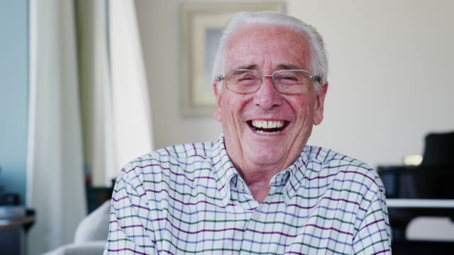 Happy senior man at home laughing to camera, close up