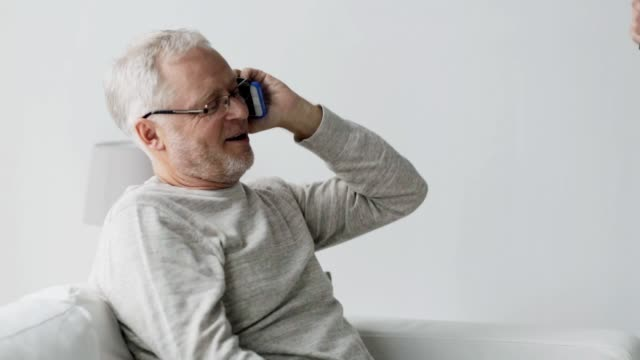 happy senior man calling on smartphone at home technology, people, lifestyle and communication concept - happy senior man dialing phone number and calling on smartphone at home dial stock videos & royalty-free footage