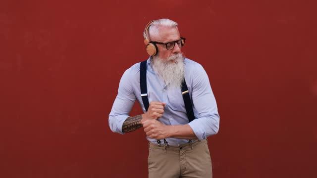 ヘッドフォンで屋外で音楽を踊り、聴く幸せなシニア男性 - 喜びに満ちた高齢者のライフスタイルと技術 - あごヒゲ点の映像素材/bロール