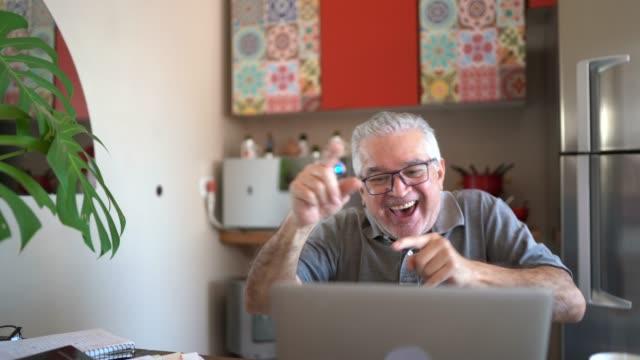 felice uomo anziano che balla mentre guarda laptop a casa - disinvolto video stock e b–roll