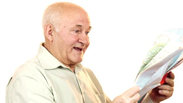 Happy senior man using a map smiling joyfully video