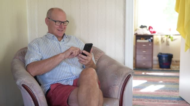 Homem sênior feliz que usa o telefone no sofá em casa - vídeo
