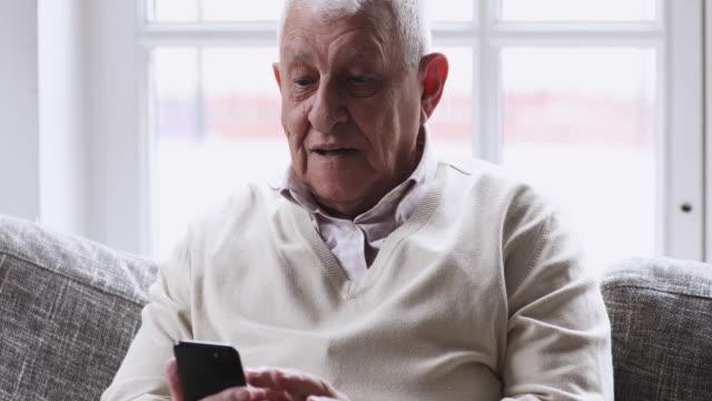 glad senior man med smart telefon avkopplande på soffan - videor med medicinsk undersökning bildbanksvideor och videomaterial från bakom kulisserna