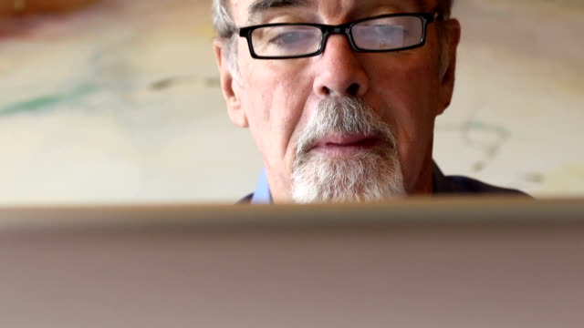 Happy Senior Man using Technology Close up of a happy senior man using technology. satisfaction stock videos & royalty-free footage