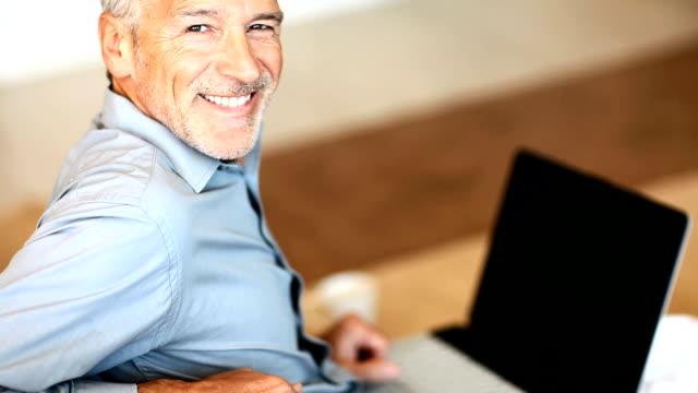 Happy senior man working on laptop video