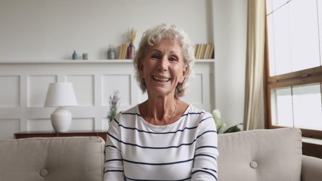 happy senior old grandmother talking to camera at home - nonna video stock e b–roll